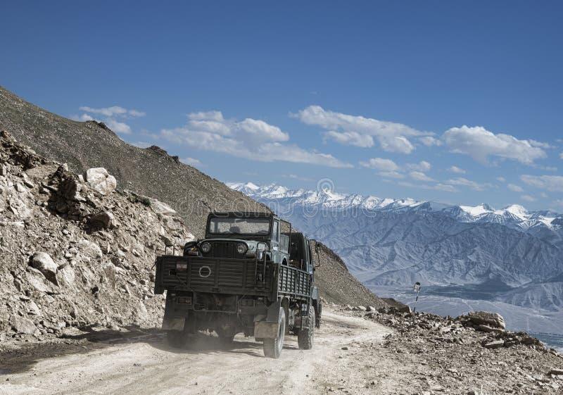 Vervoer van legerauto op een truk onder toneelberglandschap stock foto's