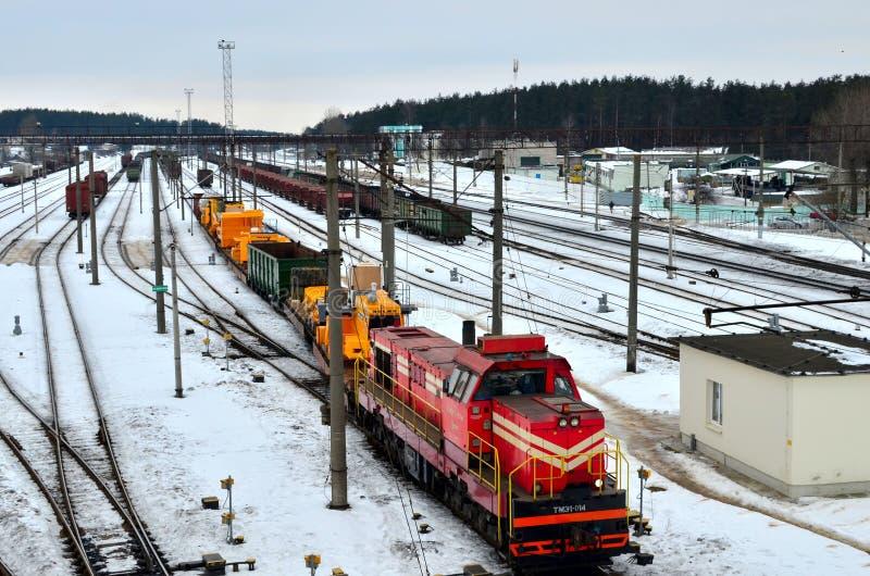 Vervoer van stortplaatsvrachtwagens Belaz per spoor Zware gele die mijnbouwvrachtwagen op een spoorwegplatform wordt gedemonteerd stock afbeelding