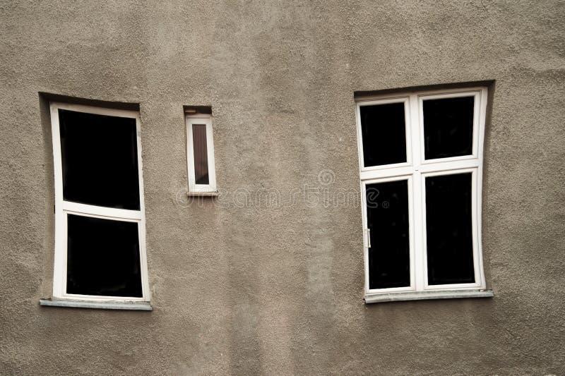 Vervormd venster met wit kader op grijze oude muurarchitectuur stock afbeelding