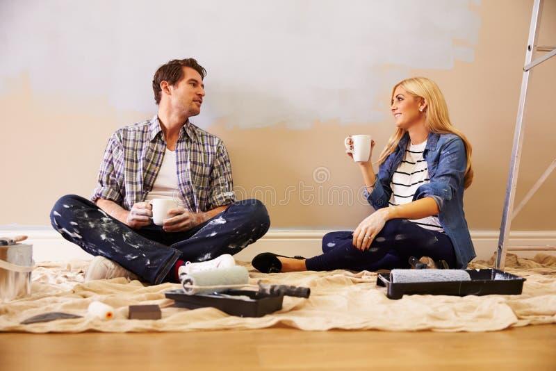 Verwachtend Paar die een Onderbreking nemen terwijl het Verfraaien van Kinderdagverblijf stock foto