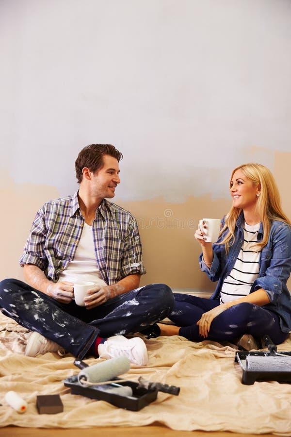 Verwachtend Paar die een Onderbreking nemen terwijl het Verfraaien van Kinderdagverblijf stock afbeelding
