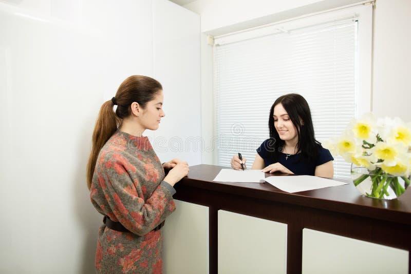 Verwalter der jungen Frau in einer zahnmedizinischen Klinik an dem Arbeitsplatz Aufnahme des Kunden lizenzfreie stockbilder