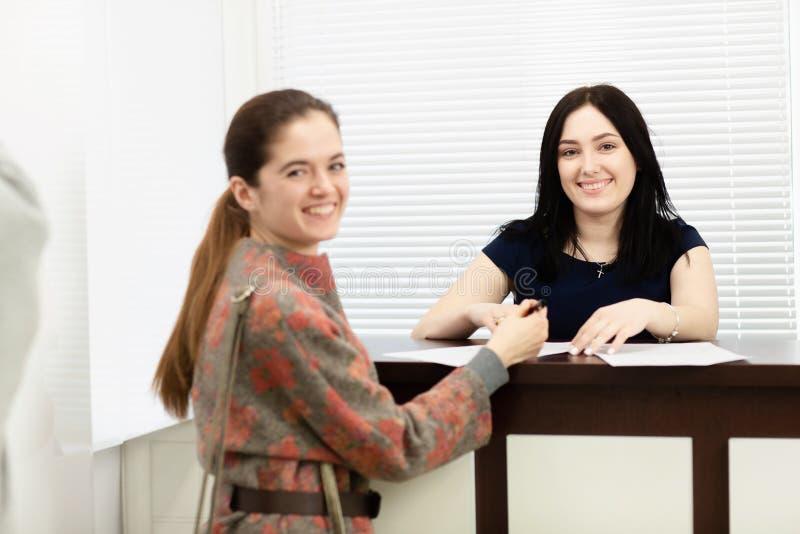 Verwalter der jungen Frau in einer zahnmedizinischen Klinik an dem Arbeitsplatz Aufnahme des Kunden stockfotos
