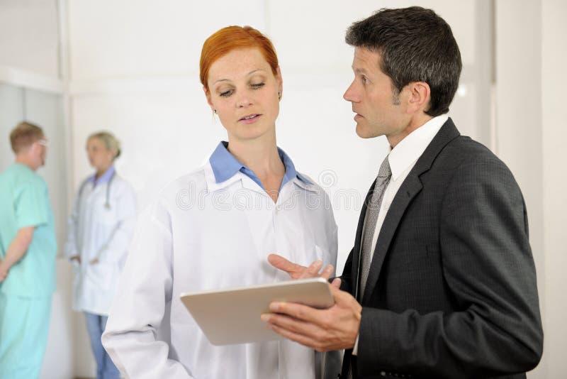 Verwalter, der mit Doktor am Krankenhaus spricht lizenzfreies stockfoto