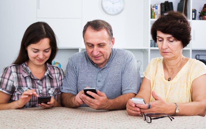 Verwandte, die Handys verwenden lizenzfreies stockbild