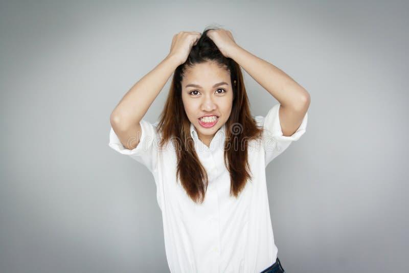 Verwar Aziatische dame die haar haar vangen dragend witte overhemd en blu royalty-vrije stock afbeelding