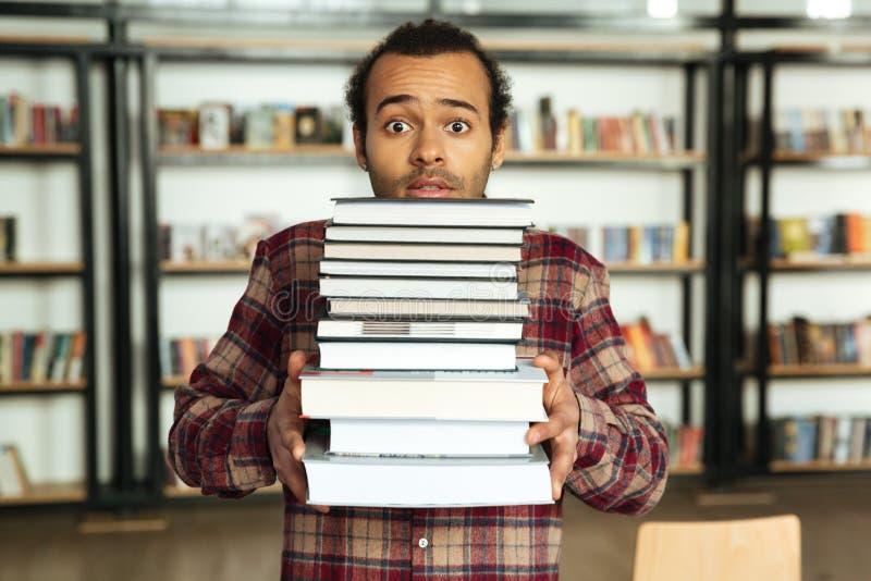 Verwarde Afrikaanse mensenstudent die zich in bibliotheek bevinden stock afbeelding