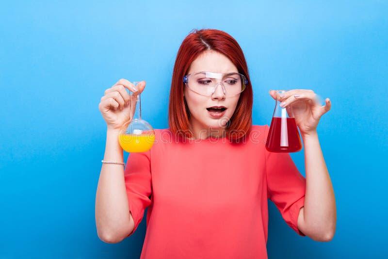 Verwarde chemicusvrouw met twee buizen met gele en rode vloeistof stock foto