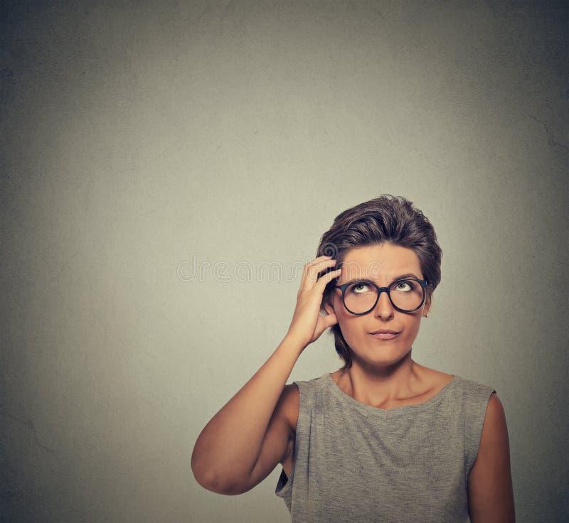Verwarde denkende verbijsterde vrouw in glazen het krassen van haar hoofd stock fotografie