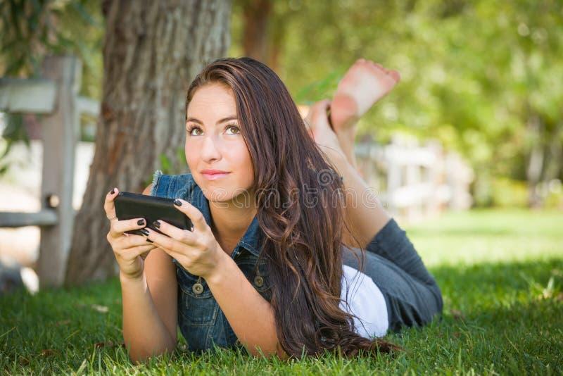 Verwarde Gemengde Rastiener Vrouwelijke Texting op Haar Slimme Telefoon stock afbeeldingen