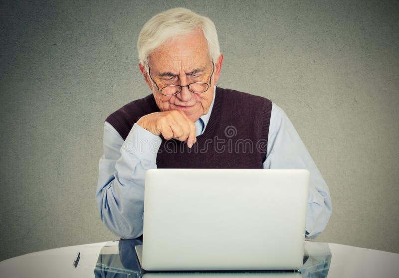 Verwarde grootvader die een PC met behulp van stock afbeelding
