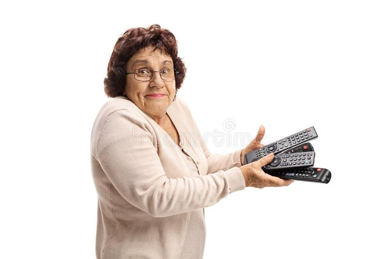 Verwarde hogere dame die een bos van remotes houden stock afbeelding