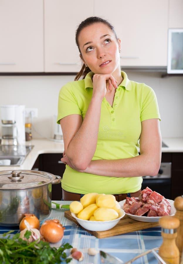 Verwarde huisvrouw bij keuken stock afbeelding