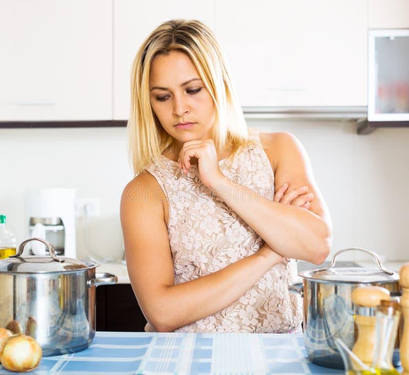 Verwarde huisvrouw in de keuken stock afbeeldingen