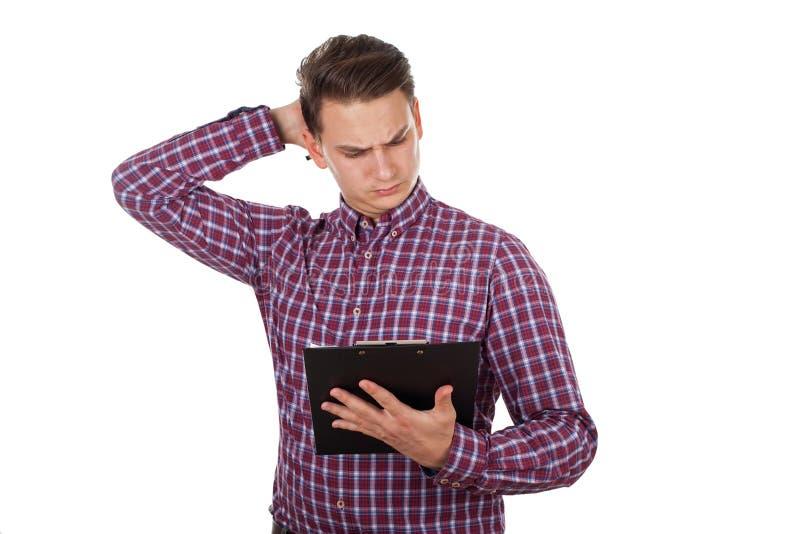 Verwarde jonge kerel die een document lezen stock afbeelding