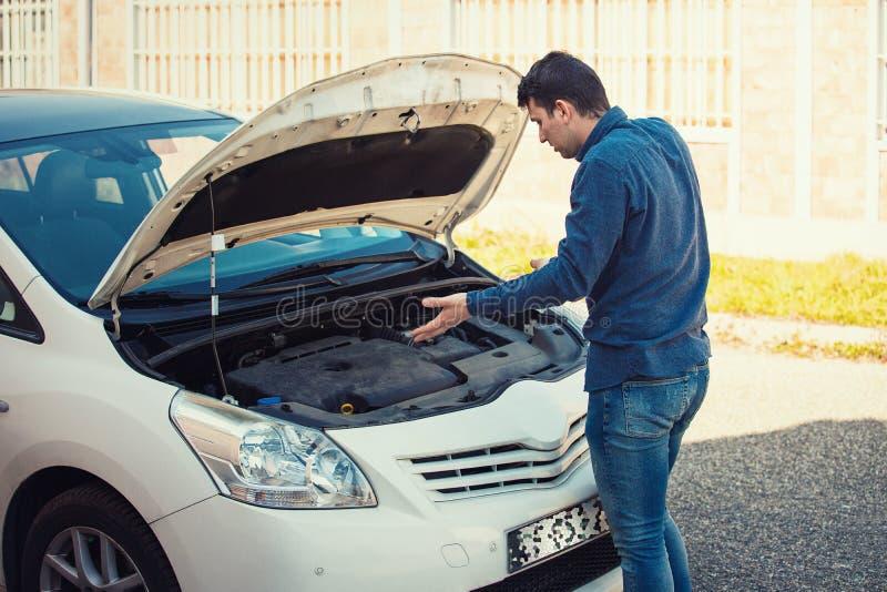 Verwarde jonge mannelijke bestuurder kijkt die die onder de geknalde kap van zijn auto wordt verward Gebroken vervoer, voertuigen stock foto's