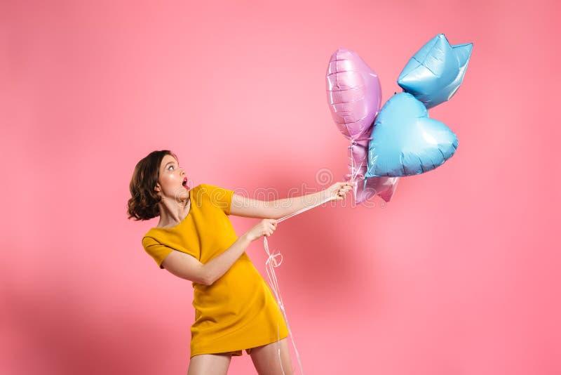 Verwarde jonge vrouw in de gele impulsen van de kledingsholding royalty-vrije stock foto
