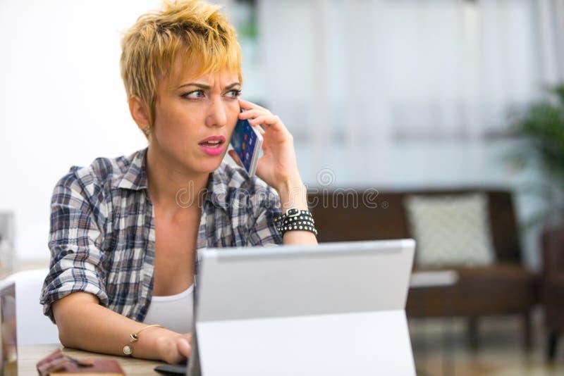 Verwarde jonge vrouw die op haar mobiele telefoon spreken stock foto