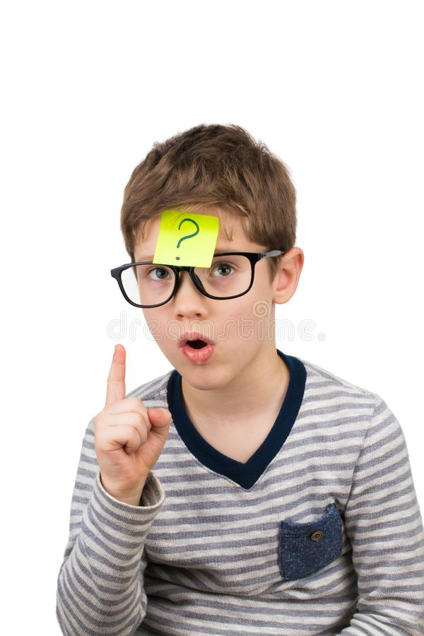Verwarde jongen die met vraagteken op kleverige nota over foreh denken stock foto's