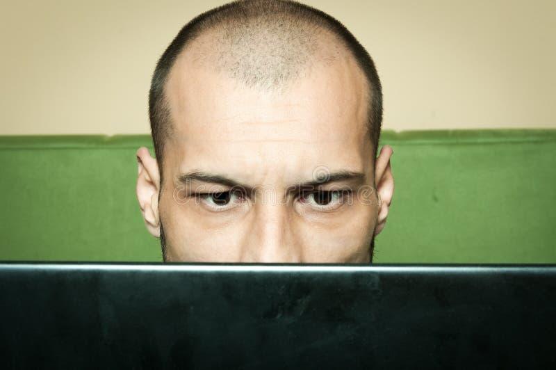 Verwarde kale mens die bij zijn computermonitor staren stock afbeelding