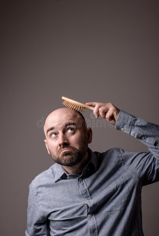 Verwarde kale mens met haarborstel stock afbeelding