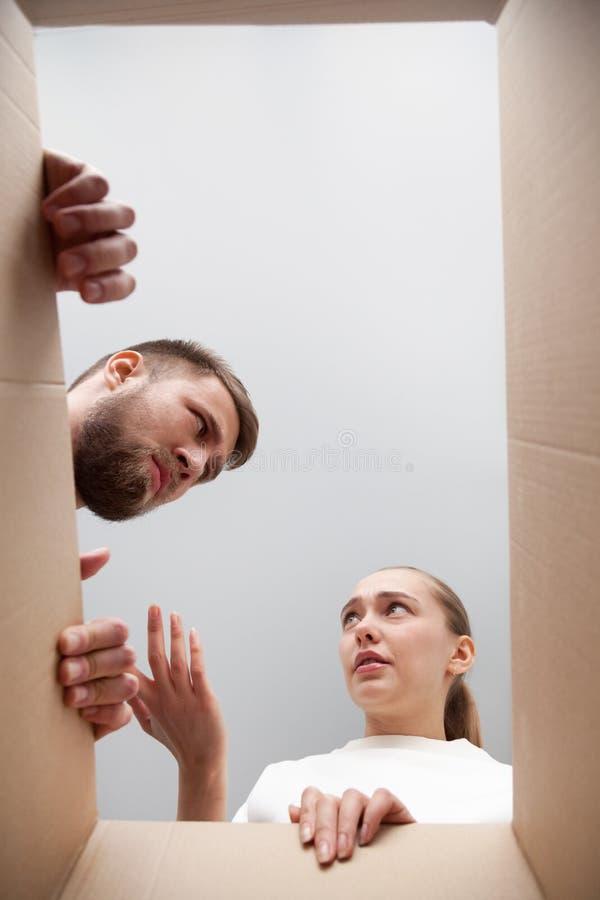 Verwarde klanten ontevreden met geleverd pakket, mening van stock afbeelding