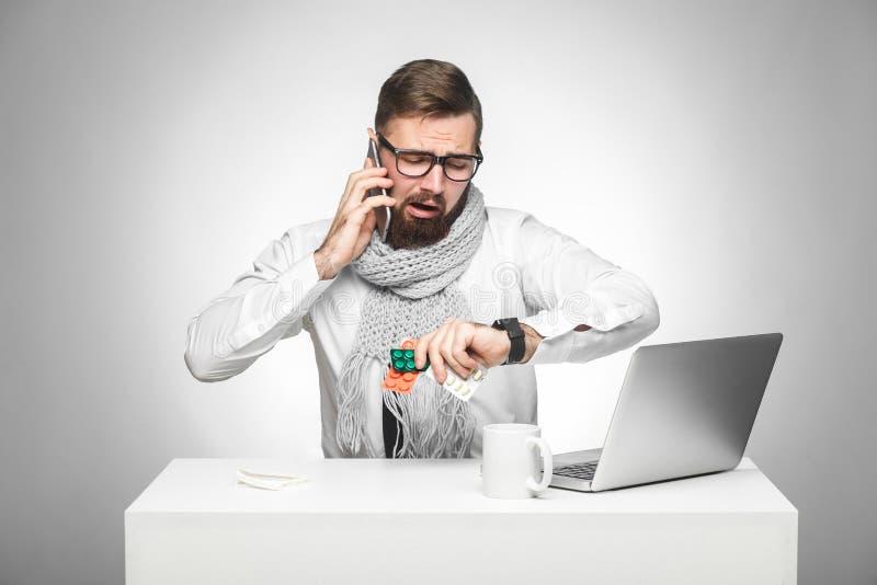 Verwarde koude zieke jonge msn in wit overhemd en de sjaal zitten in bureau op bureau en spreken ook met partner op telefoon royalty-vrije stock afbeelding