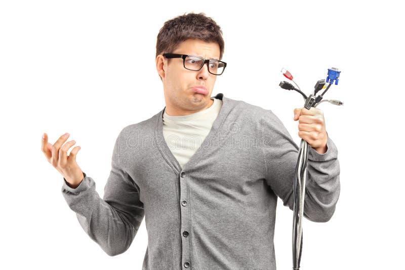Verwarde mannelijke holdings elektronische kabels stock afbeelding