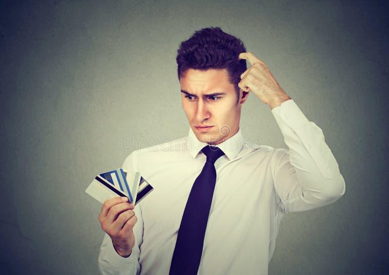 Verwarde mens die vele onzekere creditcards bekijken die te kiezen  stock foto