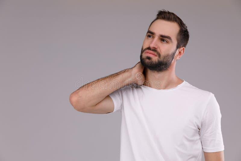Verwarde mens met een baard in een witte T-shirt op een grijze achtergrond stock fotografie