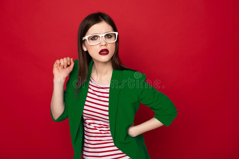 Verwarde modieuze donkerbruine die dame op rood wordt ge?soleerd royalty-vrije stock afbeelding