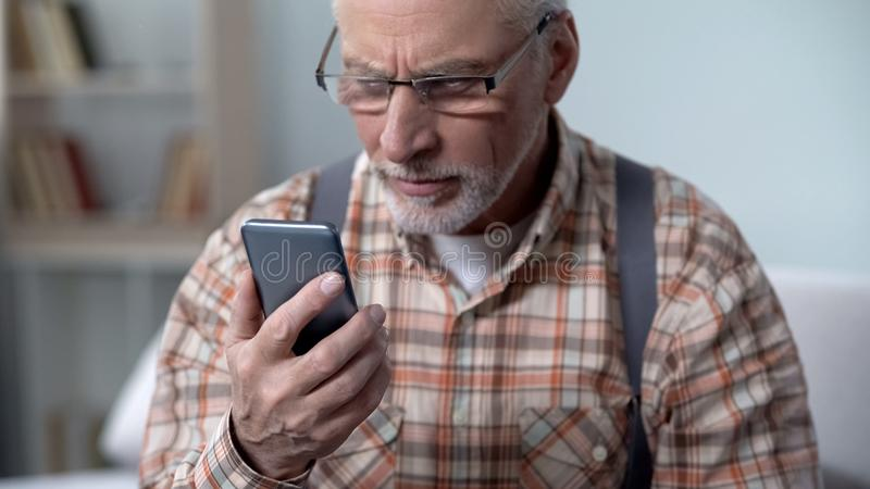 Verwarde oude mens die cellphone, nieuwe technologie bekijken ingewikkeld voor bejaarden stock foto