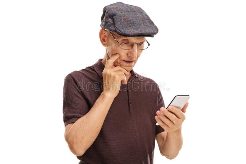 Verwarde oudste die een celtelefoon bekijken stock fotografie