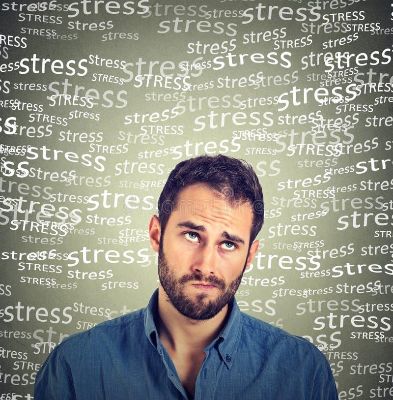 Verwarde sceptische jonge mens die het kijken denken omhoog onder spanningsdruk stock afbeeldingen