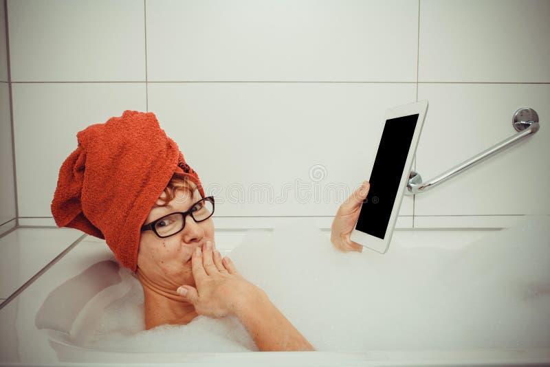 Verwarde vrouw in badkuip met tabletcomputers stock afbeelding