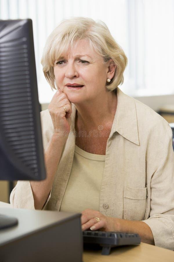 Verwarde vrouw die bij computer fronst stock fotografie