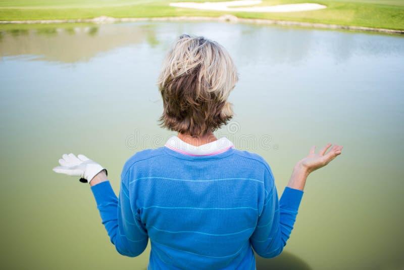 Verwarde vrouwelijke golfspeler die meer bekijken stock afbeeldingen