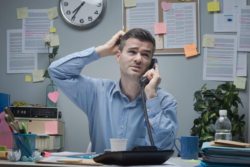 Verwarde werknemer op de telefoon stock fotografie