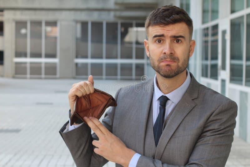 Verwarde zakenman die zijn lege portefeuille houden stock foto's