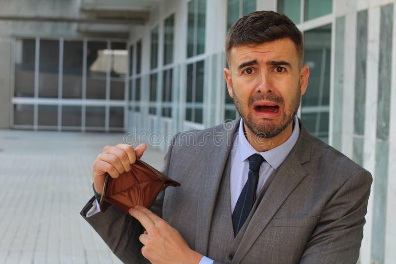 Verwarde zakenman die zijn lege portefeuille houden stock afbeeldingen