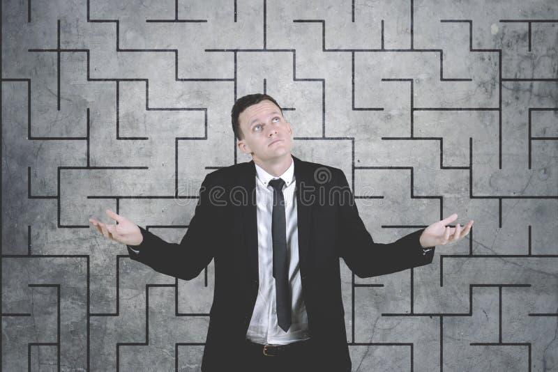 Verwarde zakenman tegen de ingewikkelde achtergrond van de labyrinttekening stock foto's