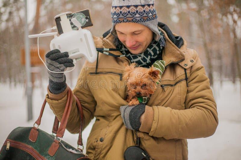 Verwarm de hond onder het jasje in de winter in de sneeuw zorg voor een hond in het koude seizoen royalty-vrije stock afbeeldingen