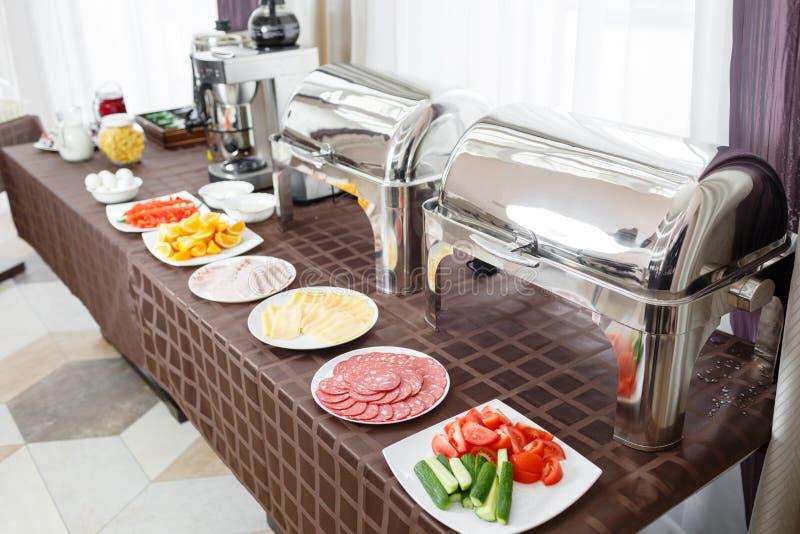 Verwarmd buffetdienbladen klaar voor de dienst Ontbijt in hotel smorgasbord Platen met verschillend voedsel royalty-vrije stock foto