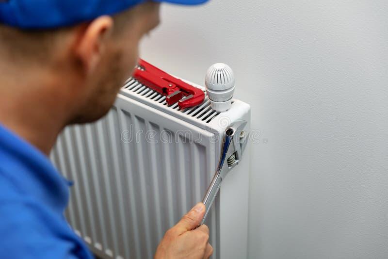 Verwarmingssysteeminstallatie en de onderhoudsdienst Loodgieter Installing Radiator stock fotografie