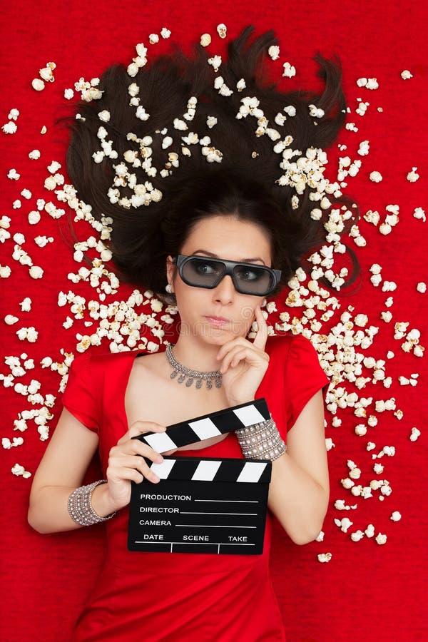 In verwarring gebracht Meisje met 3D Bioskoopglazen, Popcorn en Directeur Clapboard stock foto