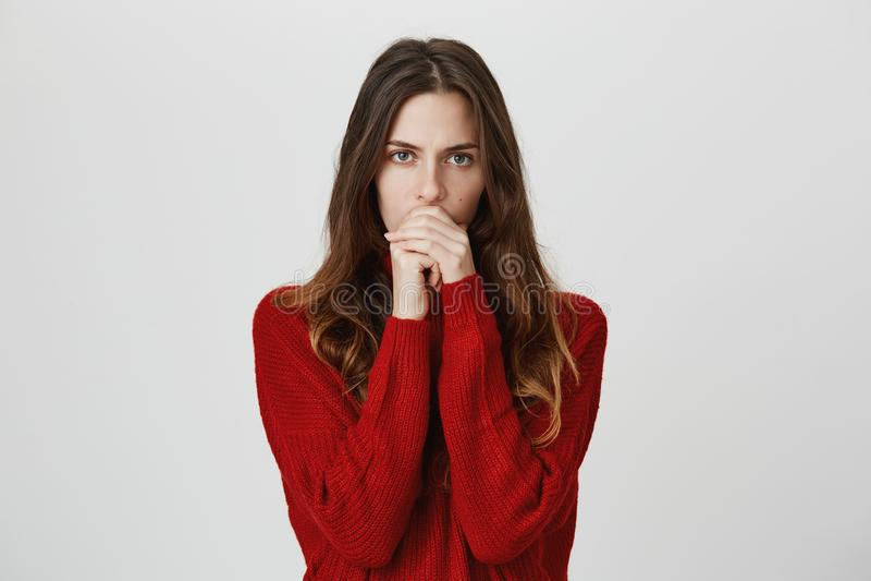In verwarring gebracht studioschot die van ernstig peinzend jong wijfje met lang haar in rode sweater sluitende mond, hebben zich stock foto's
