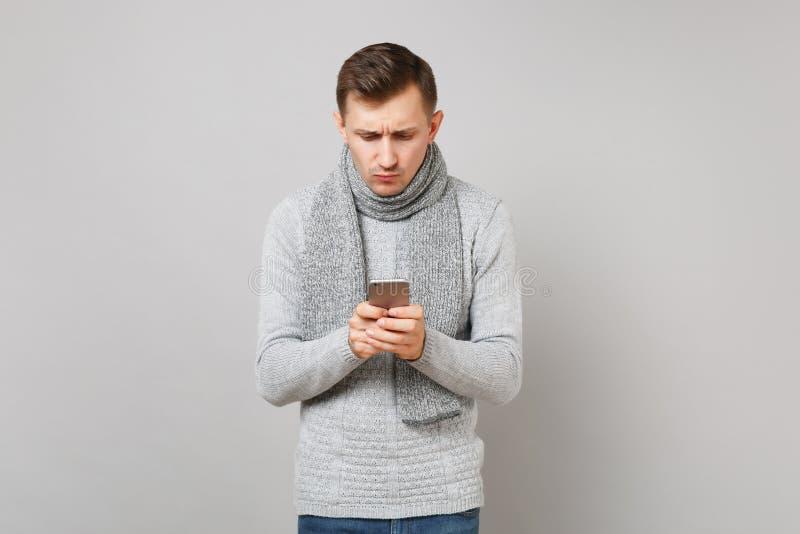 In verwarring gebrachte jonge mens in grijze sweater, sjaal die mobiel die telefoon het typen sms bericht gebruiken op grijze ach stock foto's