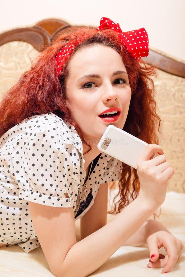 In verwarring gebrachte jonge roodharigevrouw op bank met slim royalty-vrije stock foto's