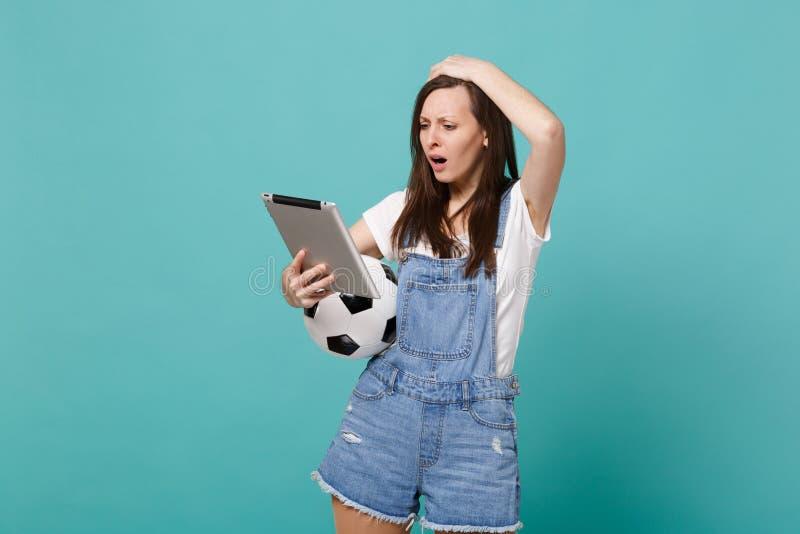 In verwarring gebrachte jonge van de de ventilatorholding van de vrouwenvoetbal het voetbalbal, die de computer die van tabletpc  stock foto