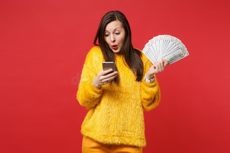 In verwarring gebrachte jonge vrouw die in bontsweater op mobiele telefoon, greepventilator kijken van geld in dollarbankbiljette royalty-vrije stock afbeeldingen